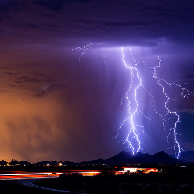 """Lightning bolts striking a mountain"" stock image"