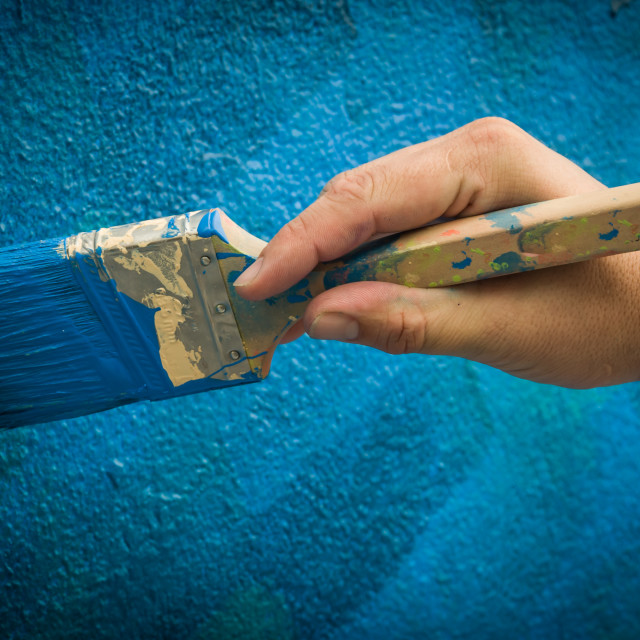 """Hand Painting Blue Wall with Paint Brush"" stock image"
