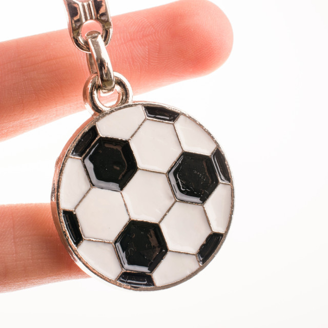 """Key holder with a soccer ball in hand"" stock image"