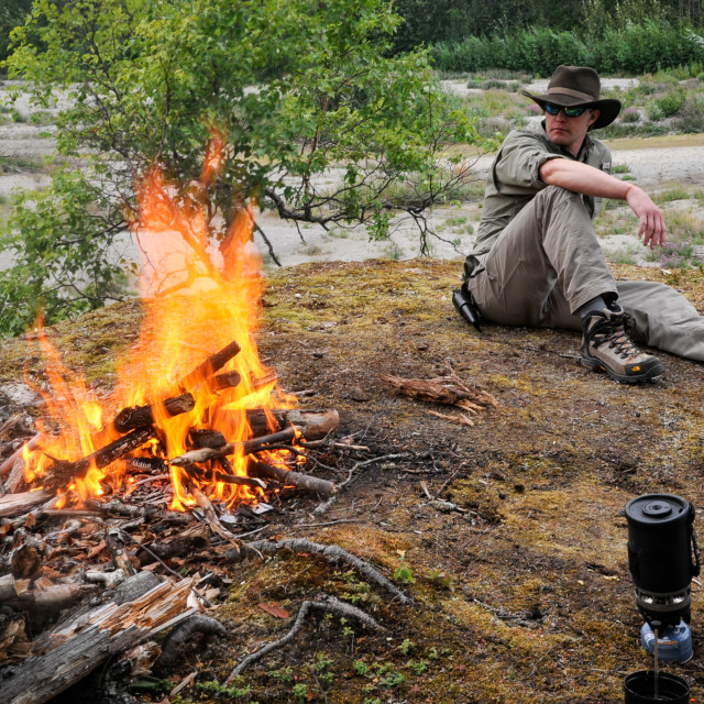 """Man in Cowboy Hat Sitting by Campfire"" stock image"