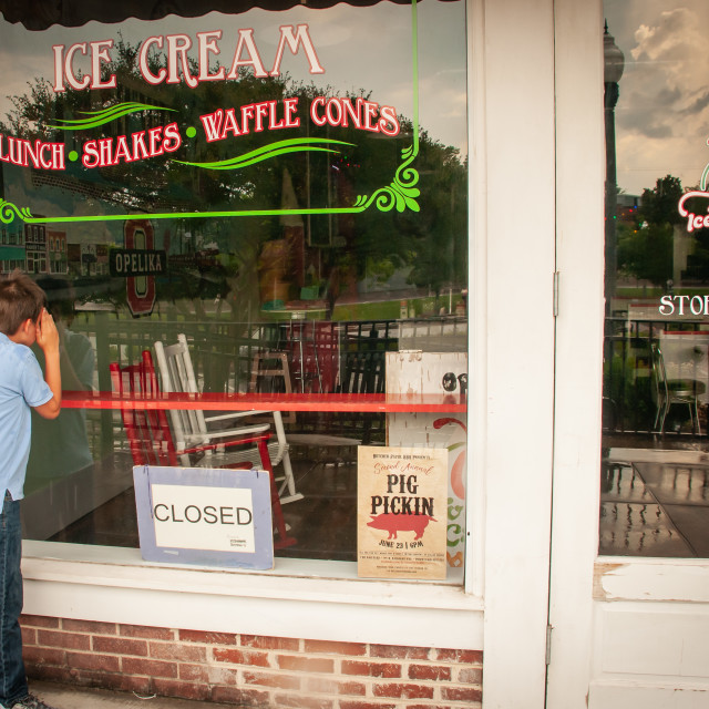 """Boy Looking in Window of Closed Ice Cream Shop"" stock image"