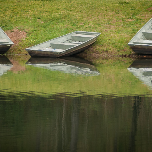 """Three Boats on the Bank of the Lake"" stock image"