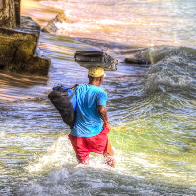 """Barbados Beach Seller In Heavy Surf"" stock image"