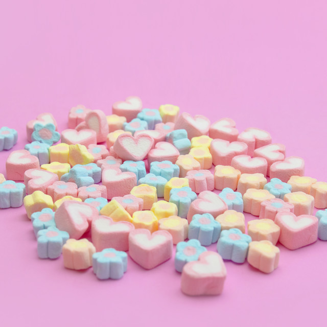 """Bunch of sweet candy marshmallows with flower and heart shapes on pink background"" stock image"