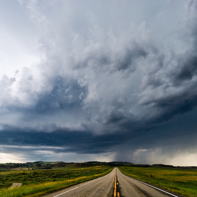 """Straight road leading to dark storm clouds"" stock image"