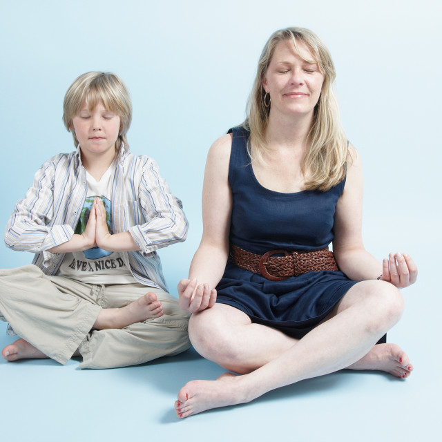 """""""Blond woman sits cross legged with her son as they both meditate"""" stock image"""