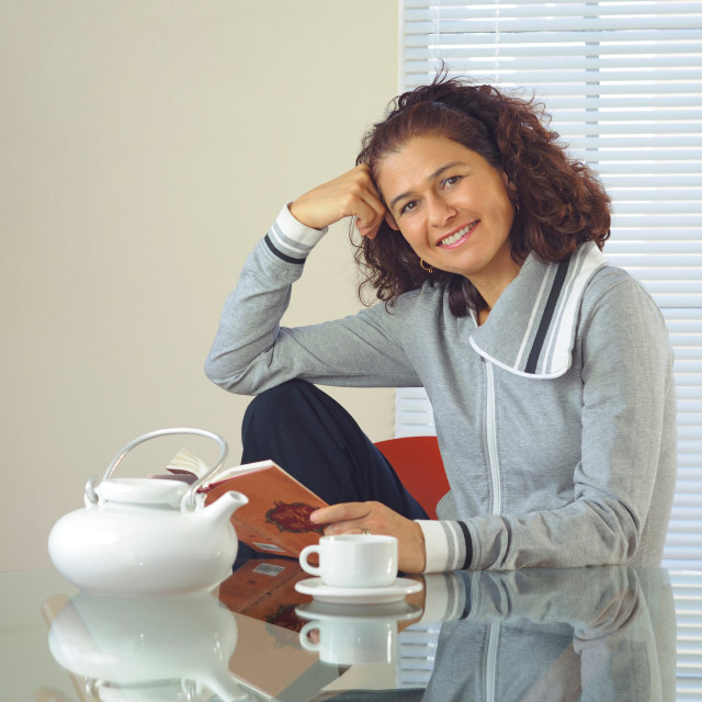 """""""Woman at a table smiling"""" stock image"""