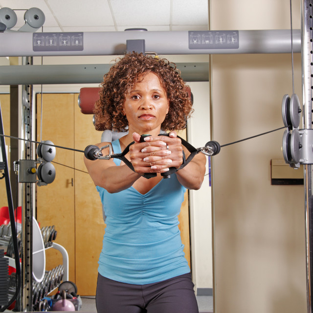 """""""Woman doing standing rows in a gym"""" stock image"""