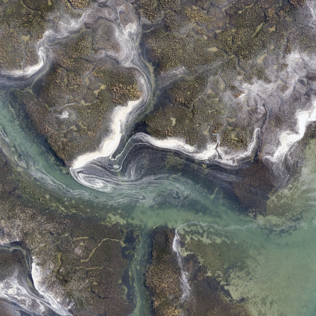 """Sea spume whipped up by recent stormy weather and the warm spring growth in the marine environment create a view fit for a painters canvas in this view taken by drone as the tide recedes at Bosham Hoe near Chichester in West Sussex."" stock image"