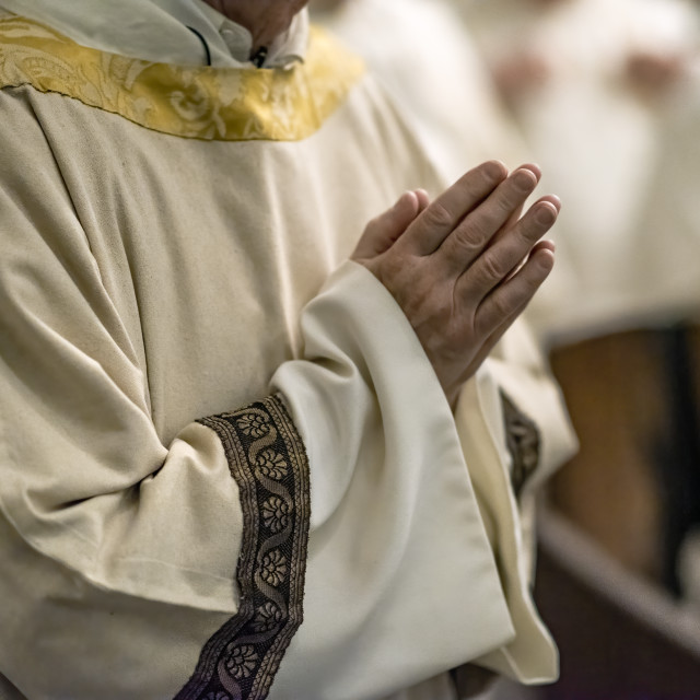 """Priest with hands folded in prayer during Catholic mass"" stock image"