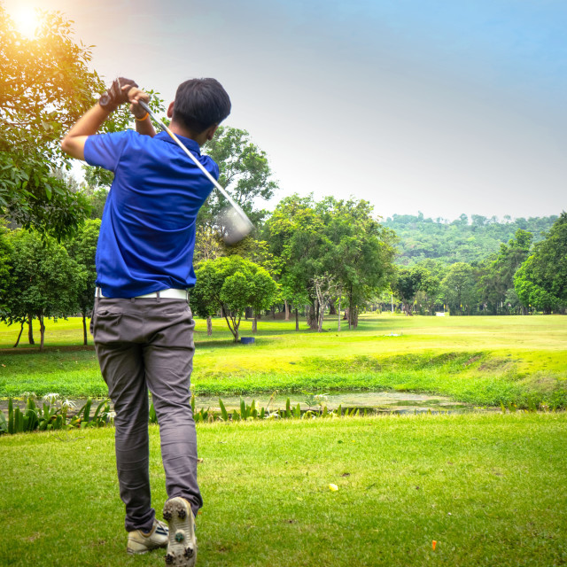"""""""Golfer playing golf on the sand in the evening golf course, on s"""" stock image"""