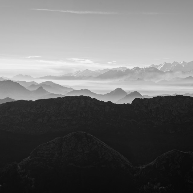 """Scenic view of silhouettes of mountains in the morning mist"" stock image"