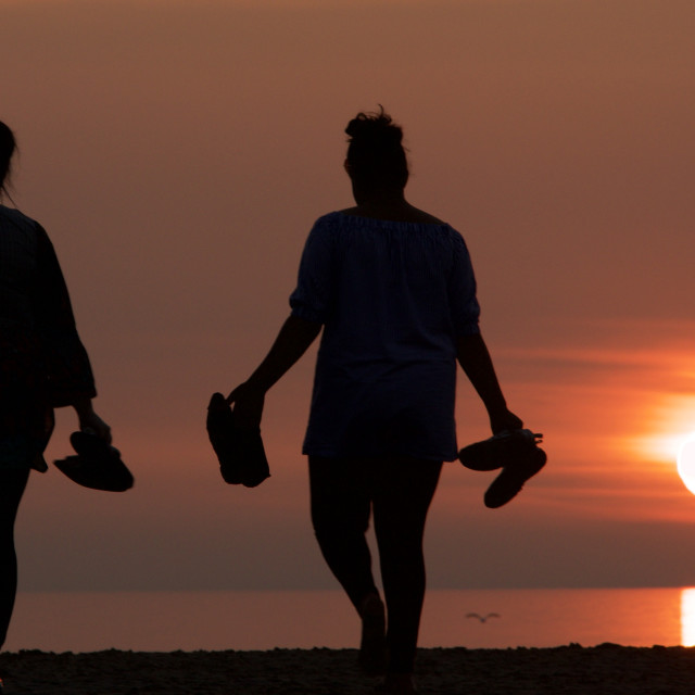 """""""Walking to the shoreline to watch the sun go down"""" stock image"""