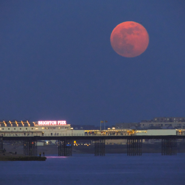 """Pink Full Moon Rising Over Palace Pier at Brighton"" stock image"
