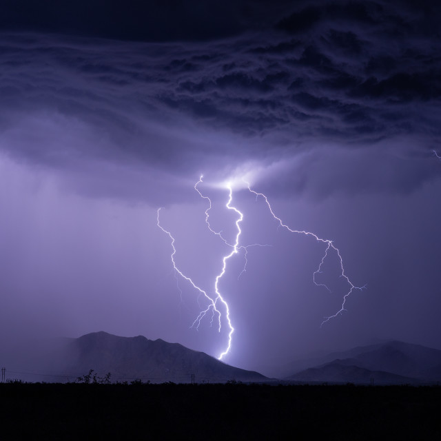 """Lightning strikes a mountain during a storm"" stock image"