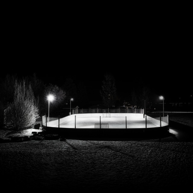 """""""A rural outdoor hockey rink beside a row of trees lit up at night in a black and white landscape"""" stock image"""