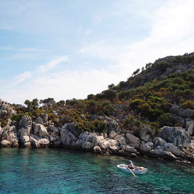 """""""A woman fishes from a rowboat off the island Kas, Turkey"""" stock image"""