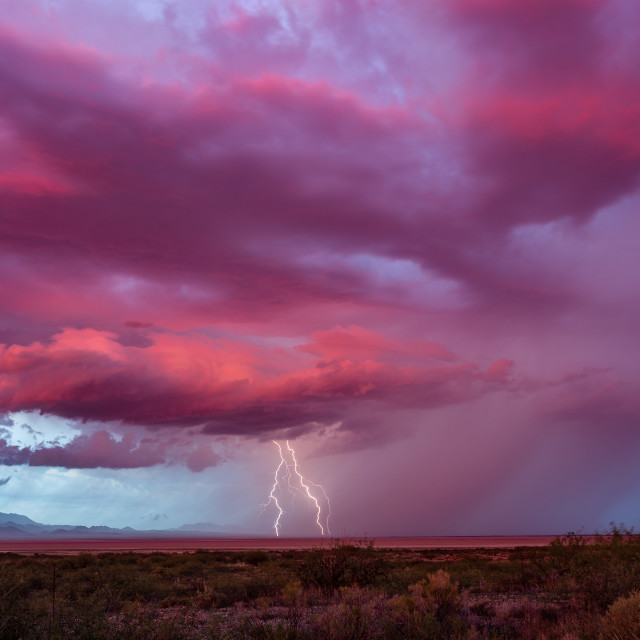 """Lightning strikes from a distant storm at sunset"" stock image"