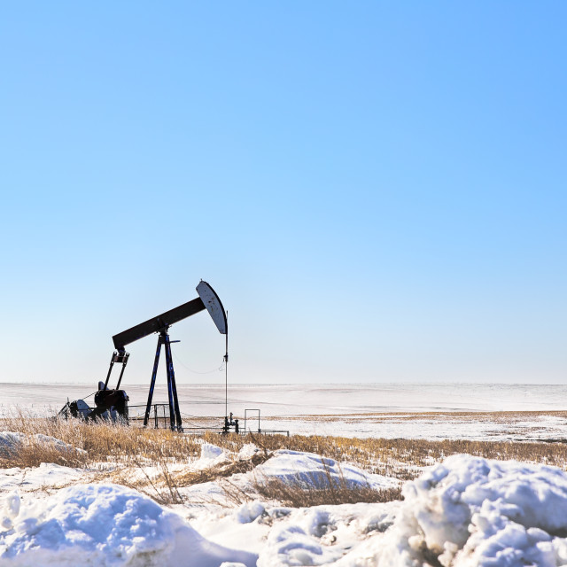 """""""An oil pump jack in a agriculture field in a winter prairie landscape"""" stock image"""