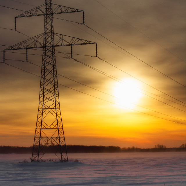 """""""A tall steel power line grid with lines running across a sunset sky in a countryside winter landscape"""" stock image"""