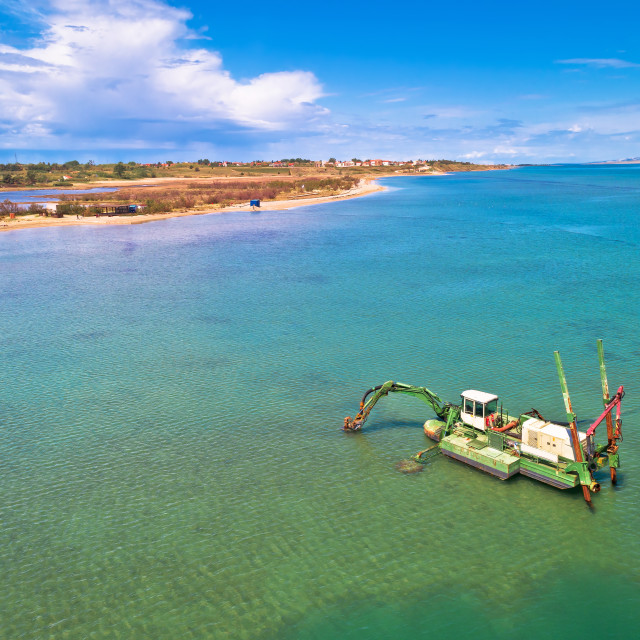 """Dredger boat excavating sand for beach in shallow water near town of Nin"" stock image"