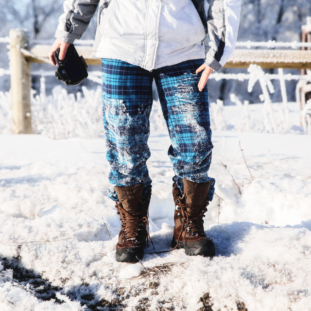 """""""The leags and waist of a woman in blue flannel checked pajamas and untied winter boots holding a camera in a snow covered pasture"""" stock image"""