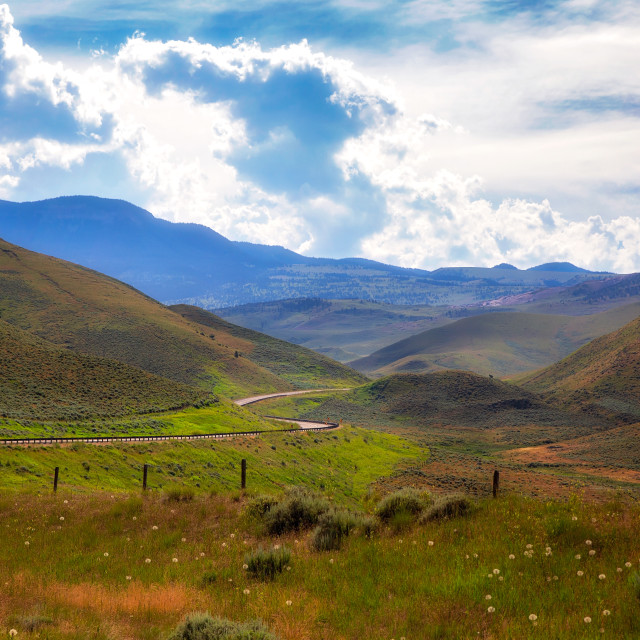 """""""A green rolling hills with a winding highway cutting through it under a cloudy blue sky in a Montana summer landscape"""" stock image"""