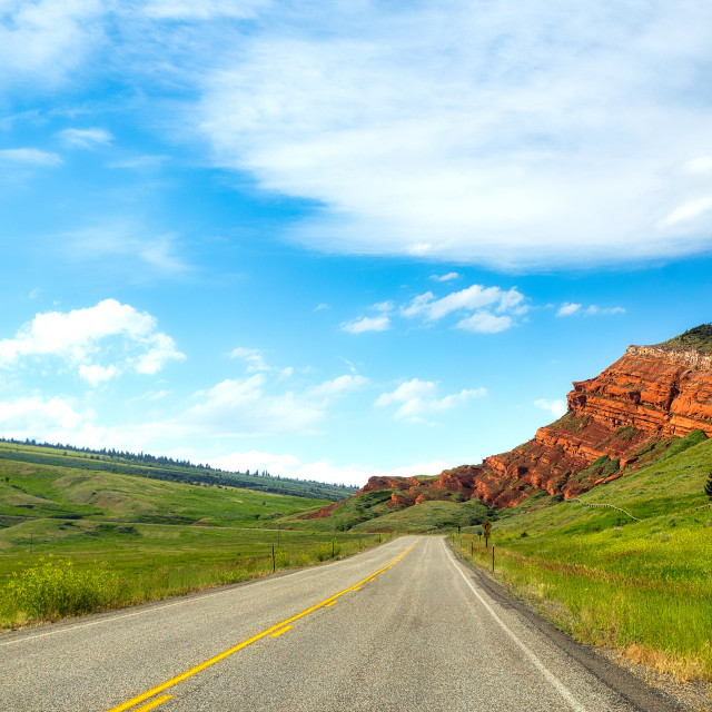 """""""Tiered red rock formation jutting toward a winding highway between rolling hills along Chief Joseph scenic highway in a summer time Montana landscape"""" stock image"""