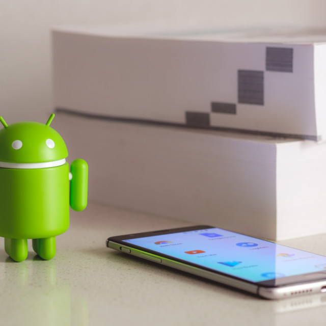 """Google Android figure with books in the background"" stock image"