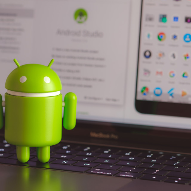 """Google Android figure standing on laptop keyboard"" stock image"