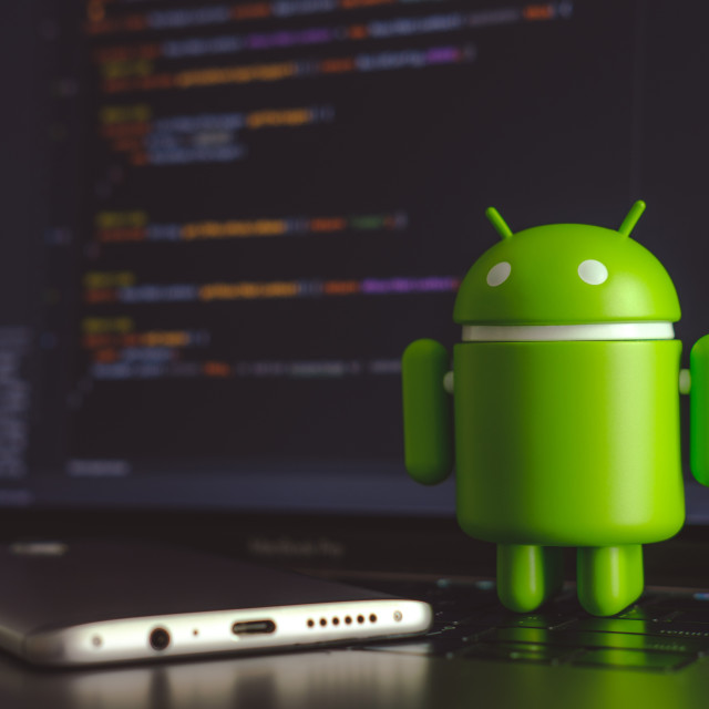 """""""Google Android figure standing on laptop keyboard"""" stock image"""