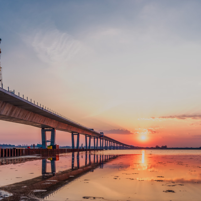 """Crown Princess Mary bridge and a construcion crane in the sunris"" stock image"