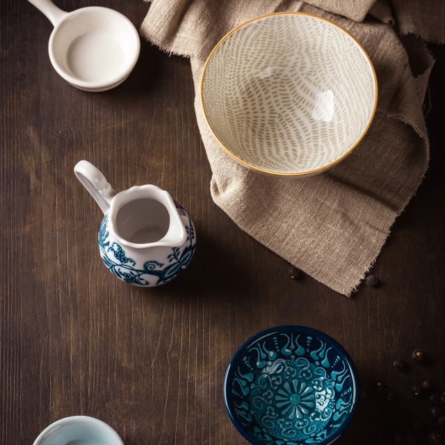 """Set of ceramic bowls placed on dark wooden board with cloth"" stock image"