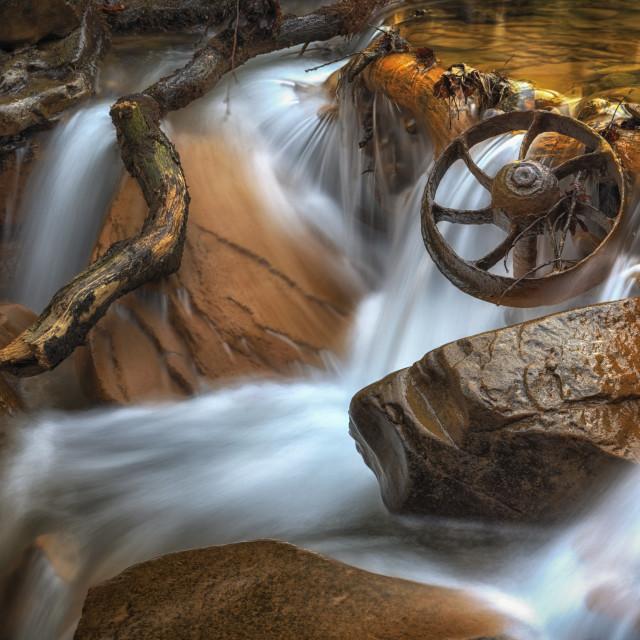 """""""Rusty coal Mining Wagon Wheel in a waterfall"""" stock image"""