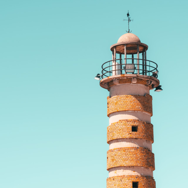 """Old Brick Stone Lighthouse At Sea On Blue Sky"" stock image"