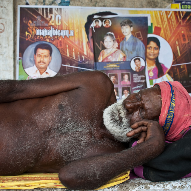 """Sadhu sleeping in the street + posters announcing the marriage of hindu couples ( India)"" stock image"