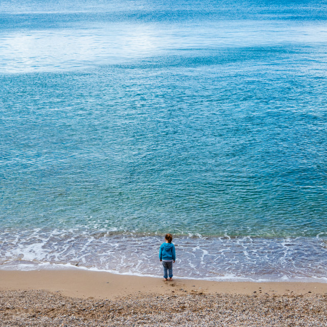 """One child alone looking at empty sea from beach"" stock image"