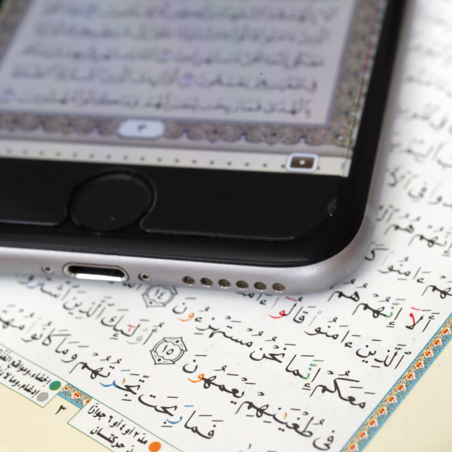 """Digital quran on a smartphone and Holy Quran book. Close-up."" stock image"