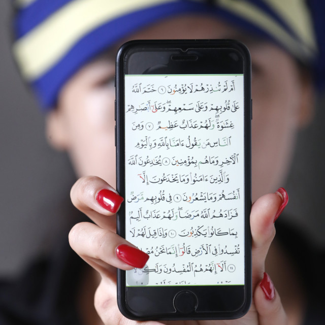 """Woman with a digital Quran on a smartphone."" stock image"