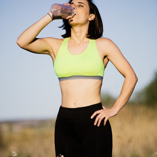 """""""Girl drinking water wearing sporty clothes in the field"""" stock image"""