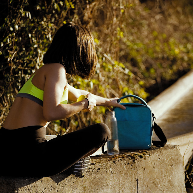 """""""Young sporty woman preparing healthy lunch in the field"""" stock image"""