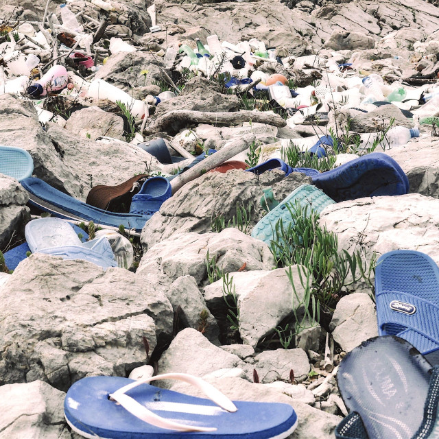 """""""Collection of Plastic Sandals on Rocky Beach"""" stock image"""