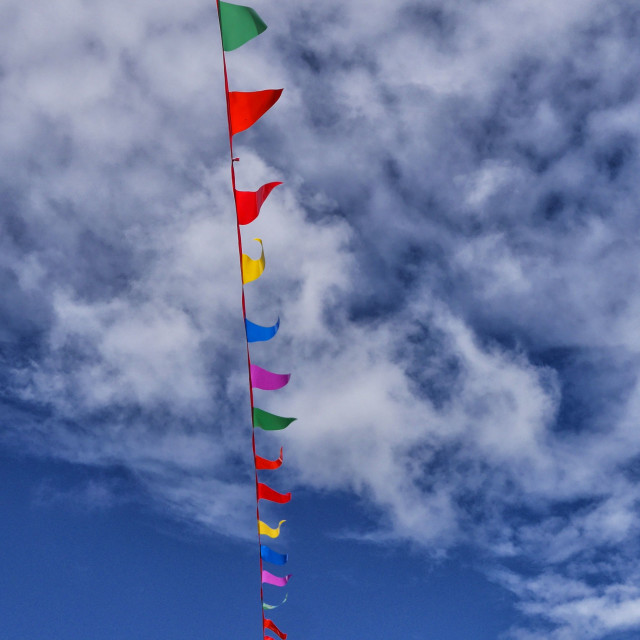 """""""Pennant Flags in a Cloudy Blue Sky"""" stock image"""