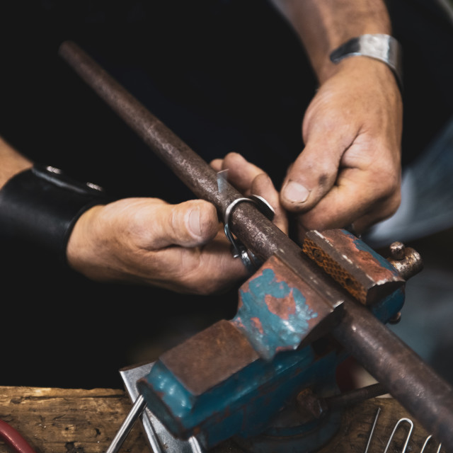 """Carpenter man hands at work with hammer and steel"" stock image"
