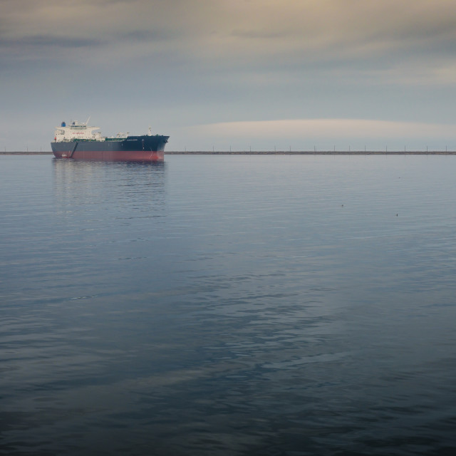 """A lone oil tanker sits in a bay."" stock image"