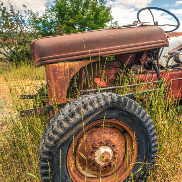 """Rusty red abandoned farm tractor"" stock image"