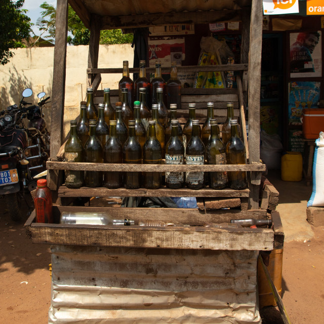 """African gas station selling gasoline in bottles along the road, Poro region,..."" stock image"