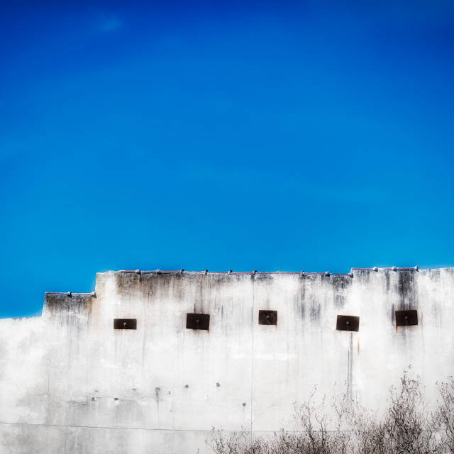 """Dramatic white wall in a blue sky"" stock image"