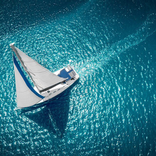 """Regatta sailing ship yachts with white sails at opened sea. Aerial view of sailboat in windy condition"" stock image"