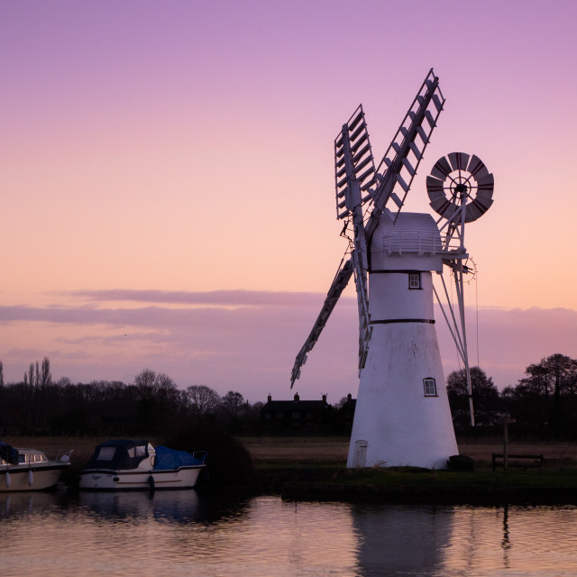 """A pink sunrise dawns over Thurne Mill in the Norfolk Broads"" stock image"